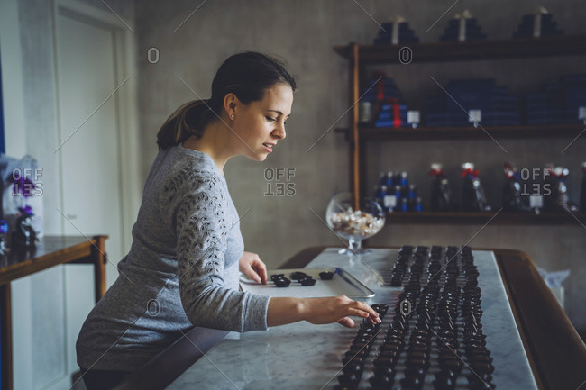 Side view of female owner arranging chocolates on table at store