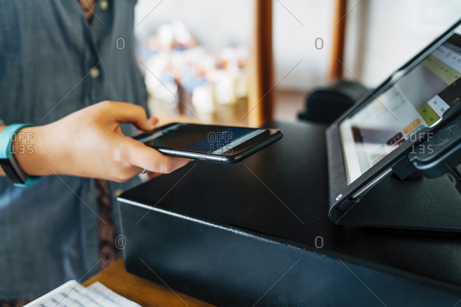 Midsection of female customer making mobile payment at store