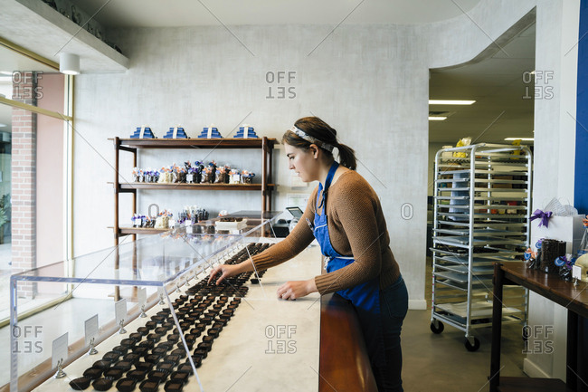 Side view of female owner arranging chocolates in display cabinet at store