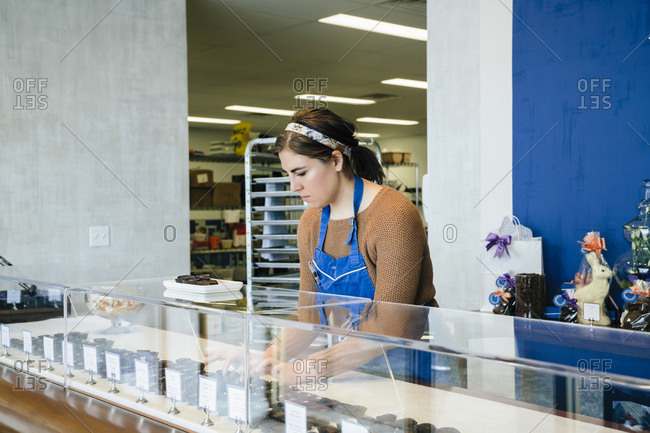 Female owner arranging chocolates in display cabinet at store