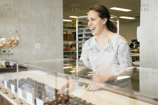 Happy owner arranging chocolates in display cabinet at store