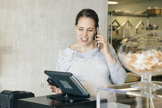 Woman talking on mobile phone while using tablet computer at store