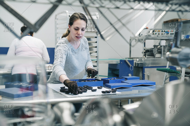 Female chef arranging chocolates in boxes while coworker working in background at factory