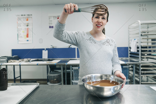 Female chef mixing chocolate in bowl at factory
