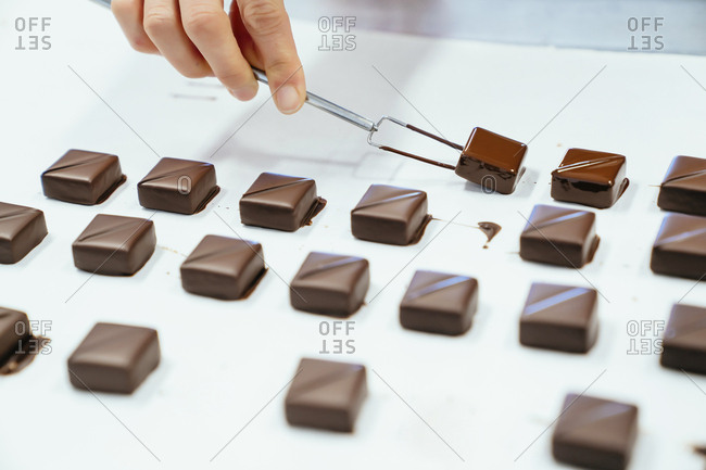 Cropped hand of chef holding chocolates with dipping fork in tray