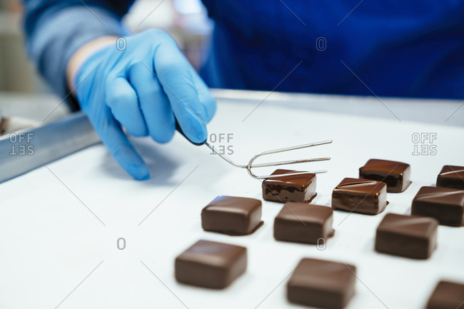 Midsection of chef holding chocolate dipped with fork in tray