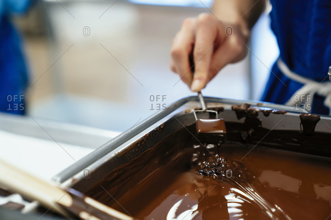Cropped hand of female chef dipping chocolate in fondue at factory