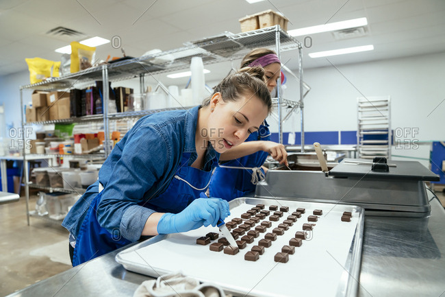Female coworkers preparing chocolates at factory
