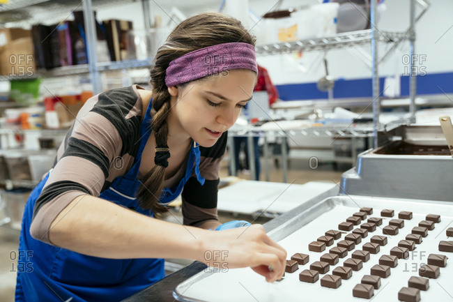 Female chef arranging chocolate pieces in tray at factory