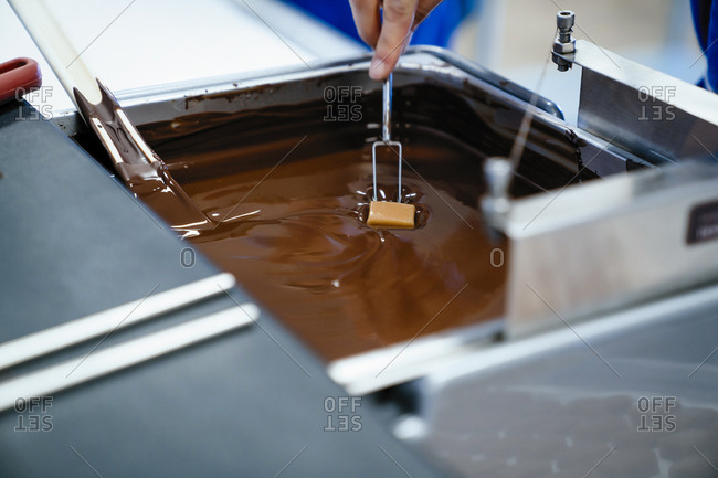 Cropped hand of female chef dipping chocolate with fork in fondue at factory