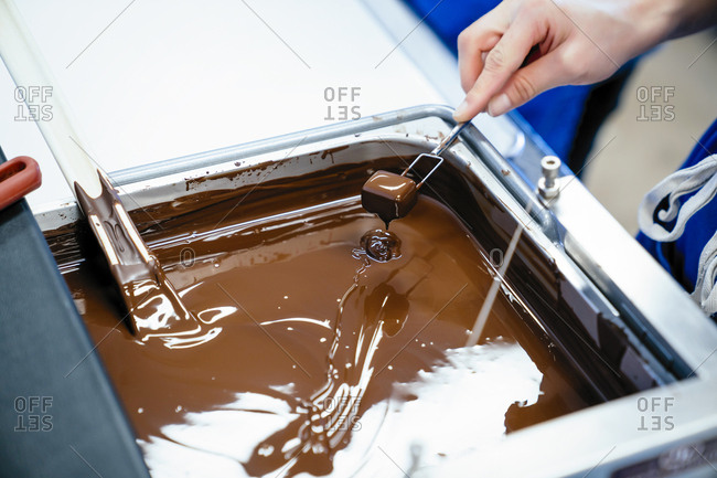 Cropped hand of female chef dipping chocolate with fork in fondue