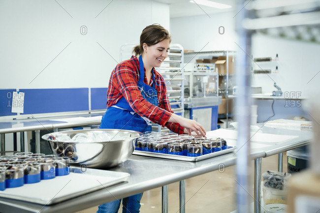 Smiling female chef arranging chocolate containers in tray at factory