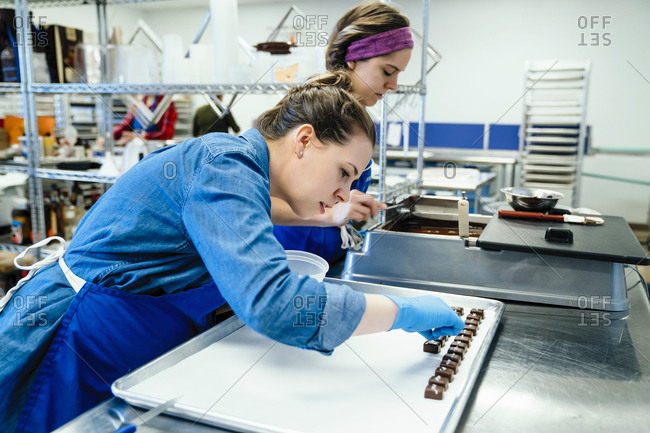 Female coworkers preparing chocolates at table in factory