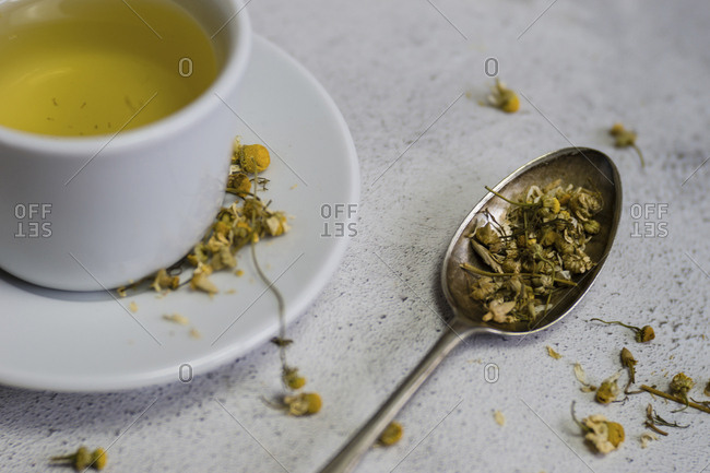 High angle view of Chamomile Tea in cup by spoon on table