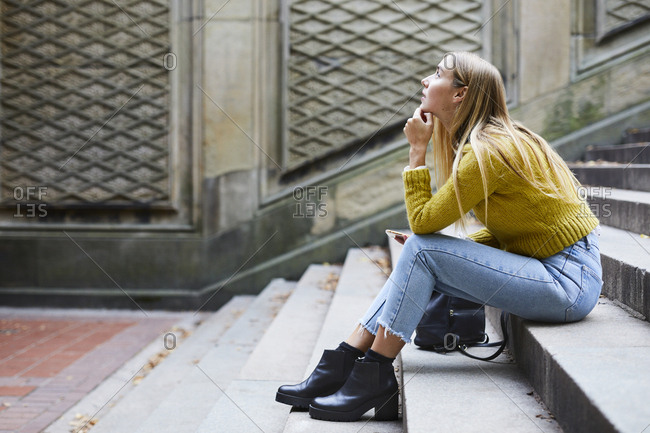 Side view of thoughtful woman sitting on steps at park