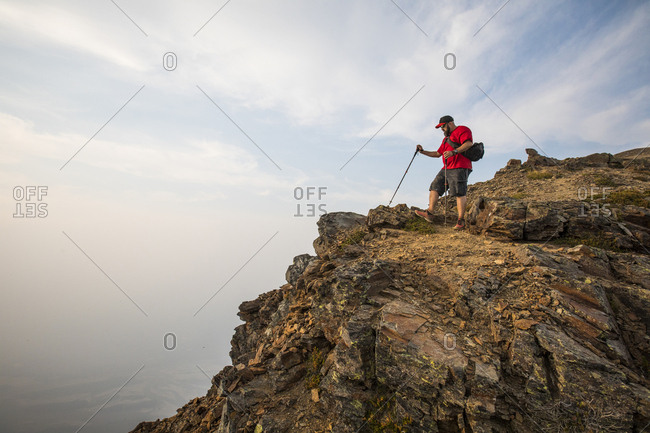 Side view of hiker with hiking poles on mountain against cloudy sky