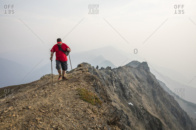 Full length of hiker using hiking poles while walking on mountain against sky