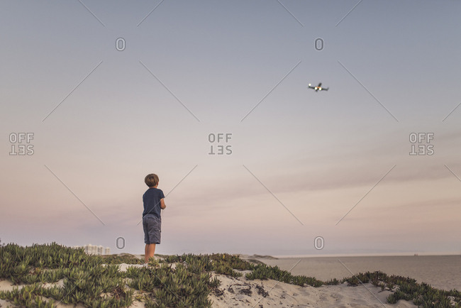 Rear view of boy looking quadcopter while standing at beach against sky