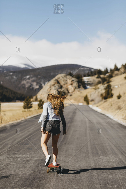 Rear view of carefree young woman skateboarding on road during sunny day