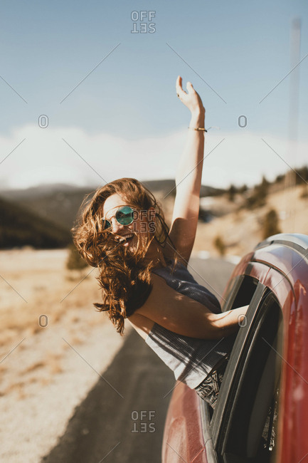 Cheerful young woman with tousled hair leaning out from car window