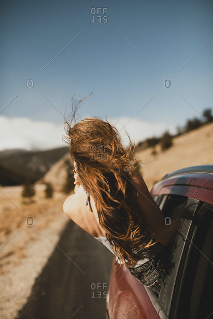 Carefree young woman with tousled hair leaning out from car window