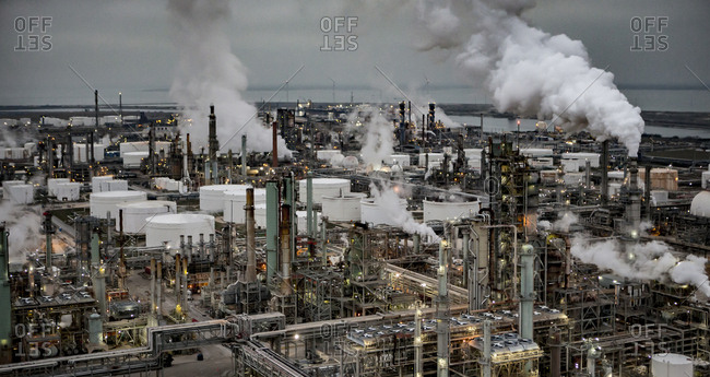 High angle view of oil refinery against cloudy sky during sunset