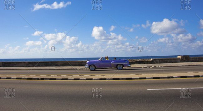 Cuba, Havana - February 13, 2017: Havana, Cuba, a shiny purple convertible classic car on an empty road with water and clouds in the background