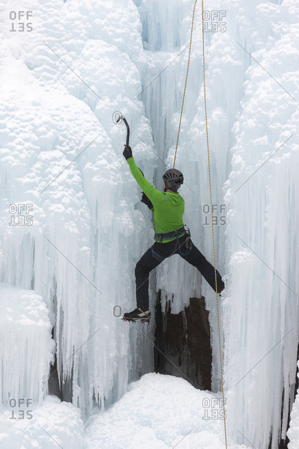 Uncompahgre National Forest, Colorado, USA - January 15, 2016: Climber ascends icy cliff face