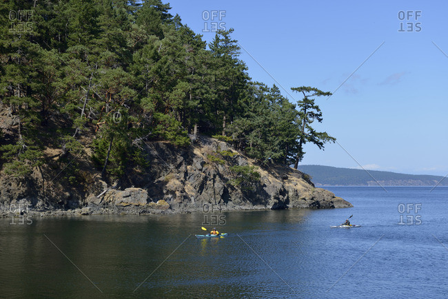 Jones Island, San Juan Islands, Washington, USA - August 21, 2015: Kayakers coming around the point on Jones Island