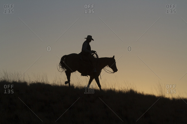 USA, Wyoming, Shell, The Hideout Ranch, Silhouette of Cowboy Riding Horse at Sunset