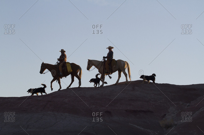 USA, Wyoming, Shell, The Hideout Ranch, Cowboys, Horses and Dogs in Early Light on Ridgeline