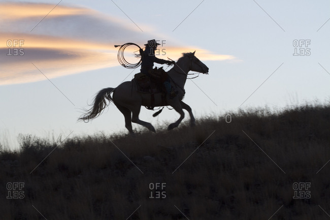 USA, Wyoming, Shell, The Hideout Ranch, Silhouette of Cowgirl with Horse at Sunset