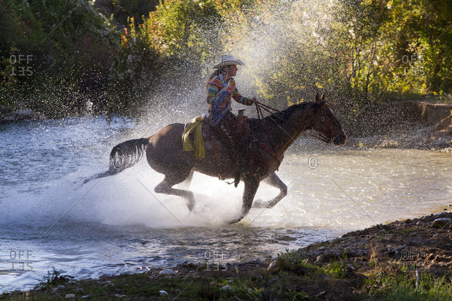 USA, Wyoming, Shell, The Hideout Ranch, Cowgirl on Horseback Crossing the Creek in a Spray of Water