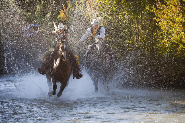 USA, Wyoming, Shell, The Hideout Ranch, Cowboy and Cowgirl on Horseback Running through the River