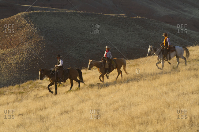 USA, Wyoming, Shell, The Hideout Ranch, Cowboys and Cowgirl Riding Horses in the Golden Light at End of Day