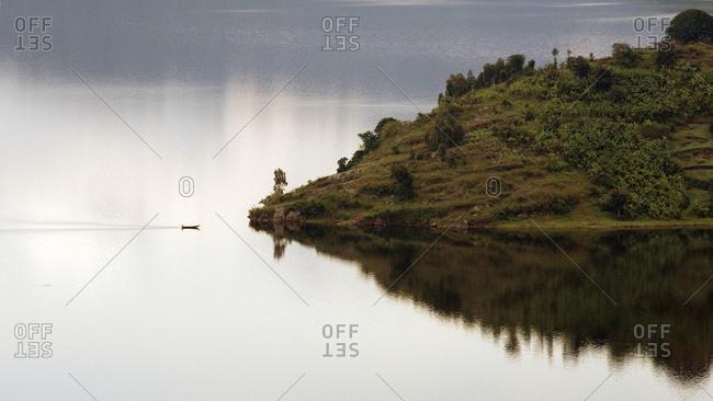 Lake Kivu, Rwanda, Africa, A small boat approaches an island in the middle of Lake Kivu