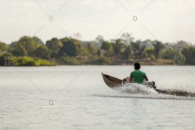 Man in a wooden motorized canoe speeds across the Amazon River near Manaus, Brazil