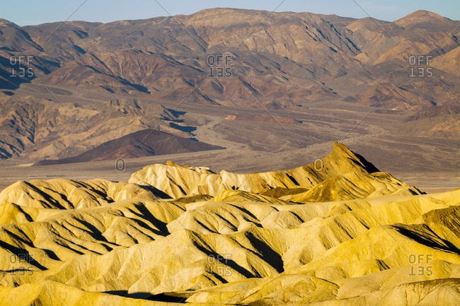 Warm light shines on the eroded hills of Golden Canyon in Death Valley National Park