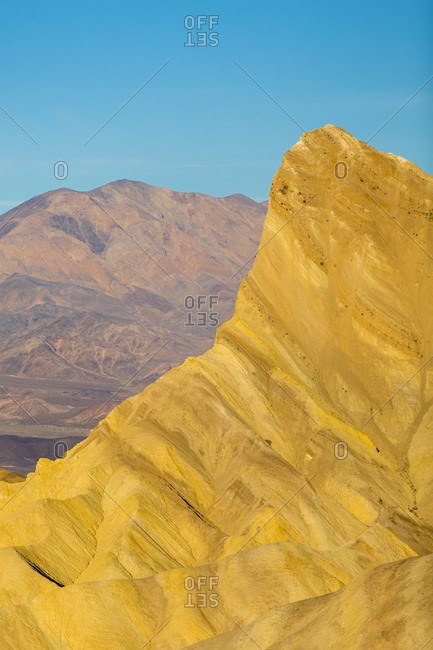 Warm light shines on Manly Beacon in the Golden Canyon in Death Valley National Park with a blue sky in the background