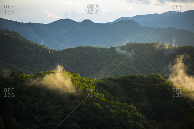 Sunlight illuminates clouds along mountain ridges layered through this sunset image taken in the Great Smoky Mountains National Park