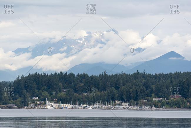 USA, Washington State, Brownsville, Clouds on Olympic Mountains, Kitsap Peninsula, Flat calm Port Orchard Narrows