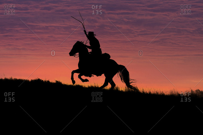 USA, Wyoming, Shell, The Hideout Ranch, Silhouette of Cowboy and Horse at Sunset