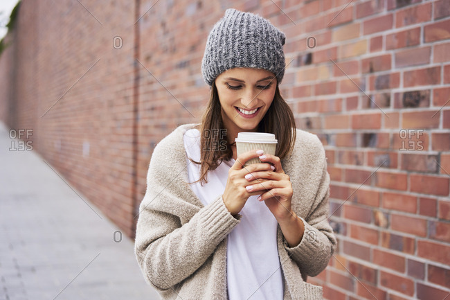 Happy woman with coffee to go