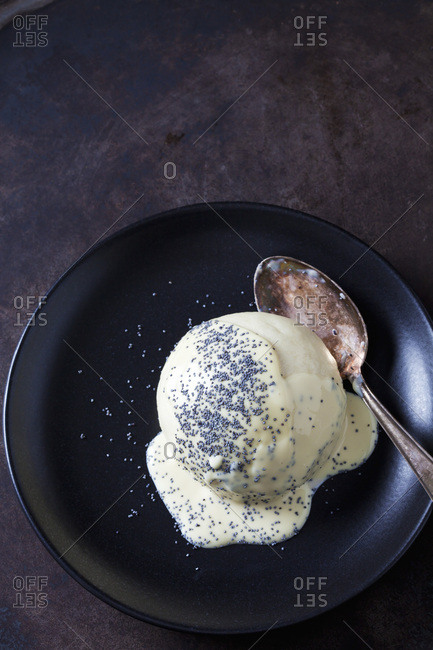Yeast dumpling with vanilla sauce and poppy seed on plate