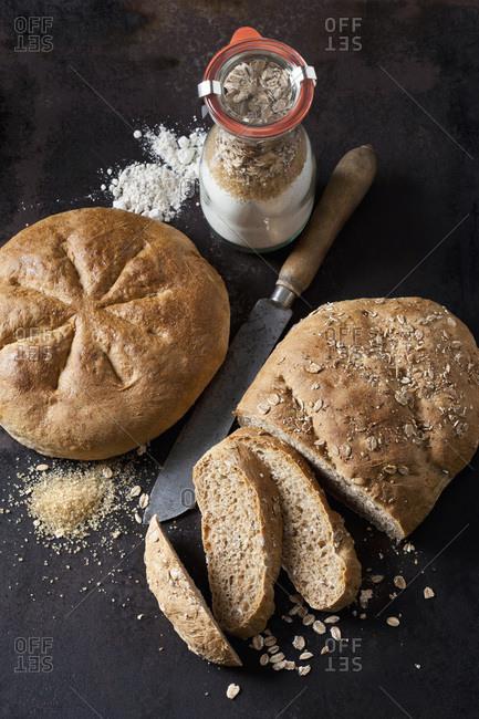 Two spelt breads and glass bottle of ingredients for preparing spelt bread