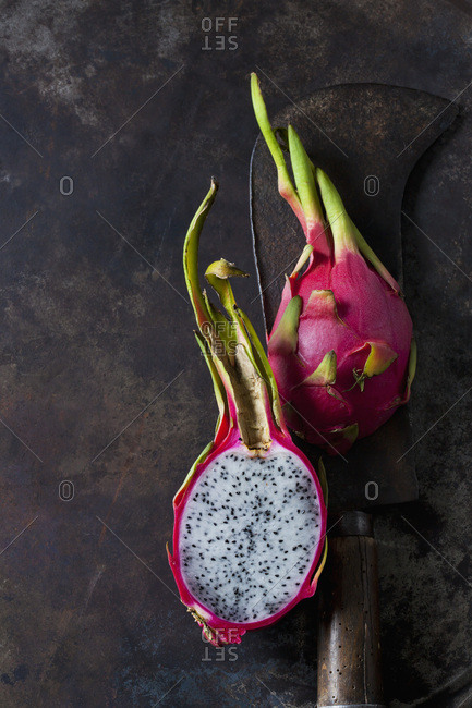 Sliced dragon fruit and cleaver on rusty metal