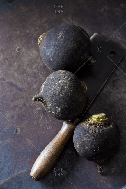 Three black radishes and an old cleaver on rusty ground