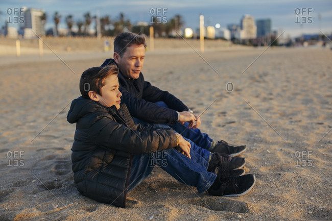 Father and son sitting on the beach