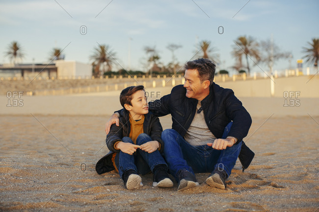 Smiling father embracing son on the beach