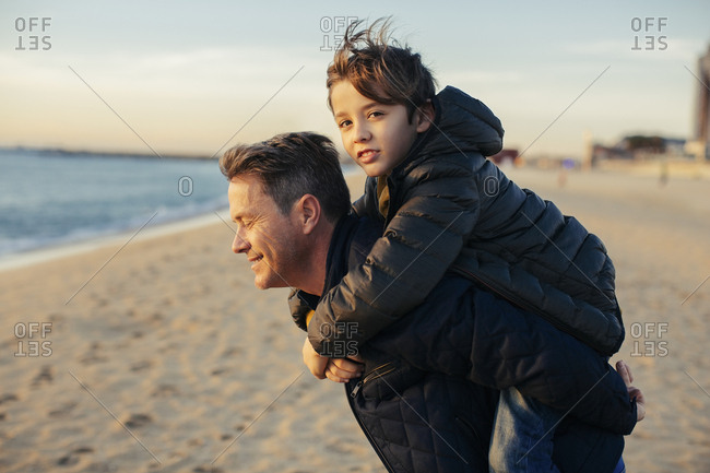 Portrait of father carrying son piggyback on the beach
